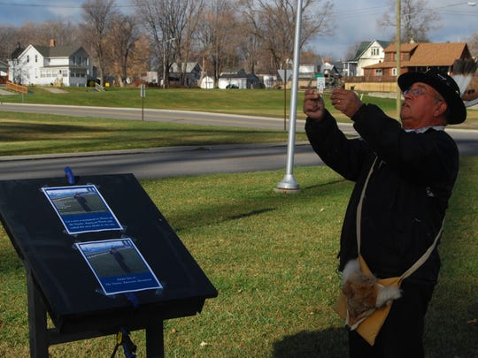 John Kennedy offers tobacco  during a ceremony at the site of a planned Native American memorial in Port Huron.
