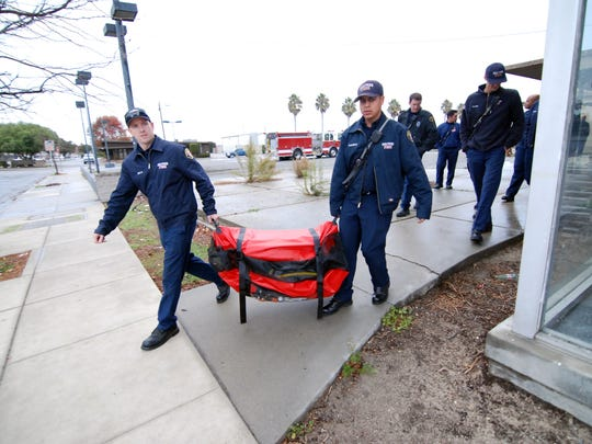Firefighters at Station 3 in Salinas move a rescue craft inside during a training session. The department is anticipating possible El Ni–o flooding.