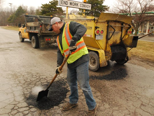 St. Clair County Road Commission employee Jim Blake levels the patching material in a pothole off 24th Street in Port Huron Township.