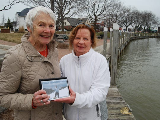 Linda Shinske, left, and Jean Larch share a photo of Larch's son, Andrew. Shinske 25 years ago rescued Andrew from the Pine River.