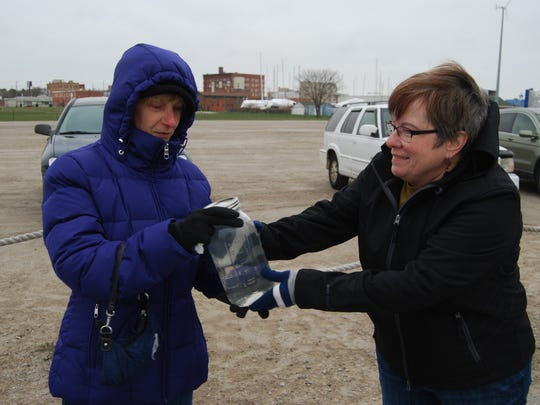 Jill McKenzie passes a mason jar of St. Clair River