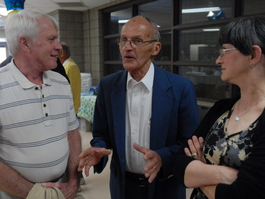 Ed Terhune, center, speaks with Craig and Sandy Tomlin.