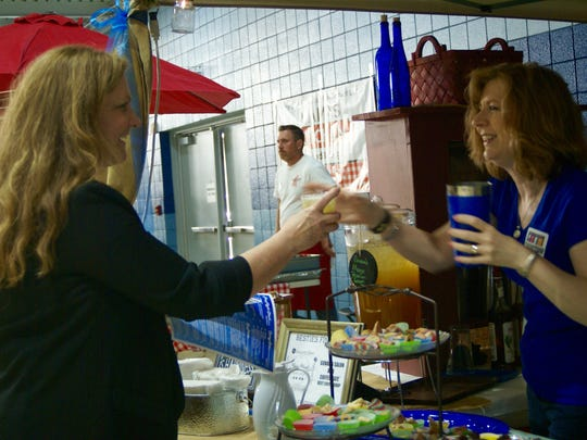 Jennifer Flanagan gets a mango passion green tea from Angela Govan, owner of Govan's Salon and Espresso Café, during the ninth annual Taste of Gallatin held at the Gallatin Civic Center on Thursday, June 2.