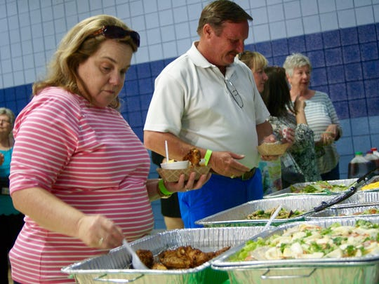 Teresa Wilson gets chicken wings from the Blossom and Cellar Door both during the ninth annual Taste of Gallatin held at the Gallatin Civic Center on Thursday, June 2.