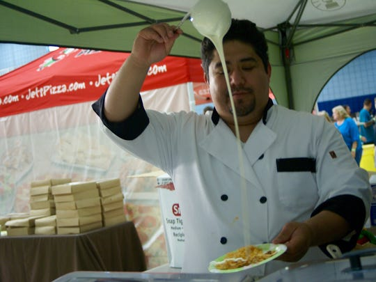 Ismael Rodriguez, manager of Cancun Lagoon, pours cheese onto food at the restaurant's booth during the ninth annual Taste of Gallatin held at the Gallatin Civic Center on Thursday, June 2.
