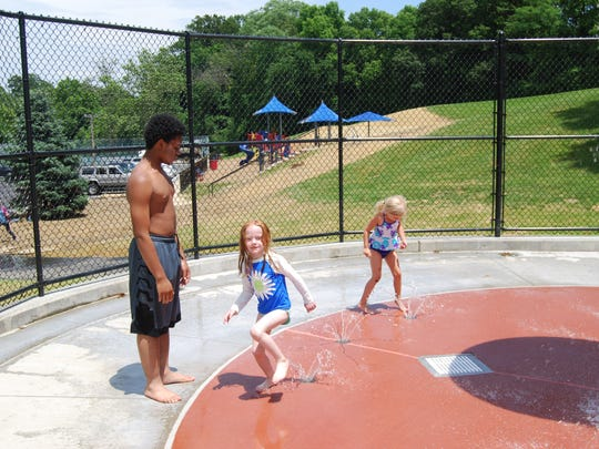 Cincinnati Recreation Commission teen counselor Rashad Ellison, left, of Madisonville, and several youngsters take advantage of the pool's new sprayground.