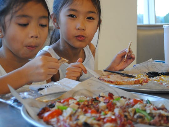 Miley Honrado, 6 and her sister Michailee, 8, enjoy the melted cheese on thier Pieology pizzas on May 19 at the Tamuning restaurant.