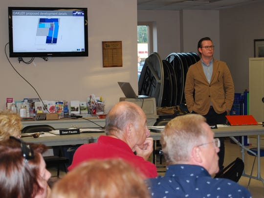Stephen Dronen, right, a development director with the Fortus Group, listens to feedback from residents during a special meeting of the Oakley Community Council to discuss zoning matters including a proposed development for the Fifth Third building on Madison Road. Residents were nearly unanimously opposed to the Fortus Group's plan to build an eight-story mixed-use structure at the site.