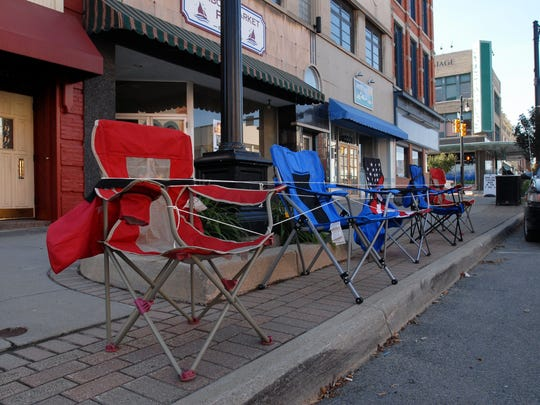 Camp chairs are tied and set together in preparation for the Rotary Parade, July 19, 2011, near 227 Huron Ave.