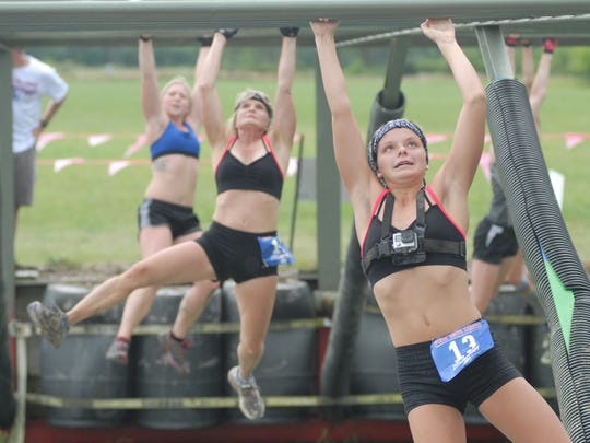 A group of runners take on the monkey bars at the SwampFoot