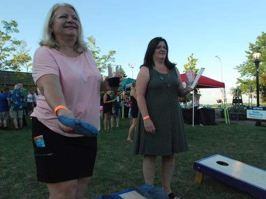 Pat Swieczowski, left, and Denise Manhart play cornhole Friday during the St. Clair Beer and Wine Festival.