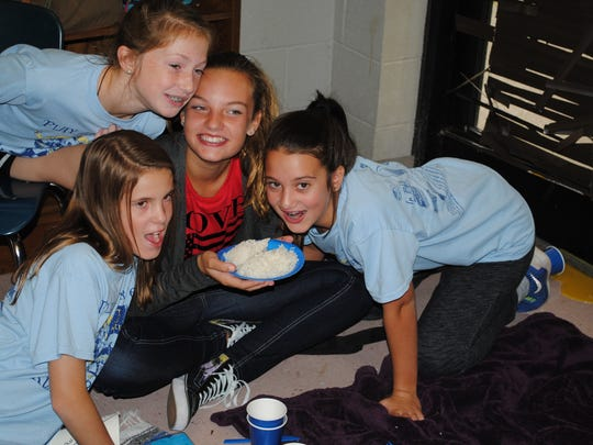 "These Thurman Francis sixth-graders got only rice and water at their ""hunger banquet,"" but classmates soon donated fresh fruit and other healthy food. Clockwise from left are Ryan Hale, Ava Lewis, Landri Hall and Madelyn Black."