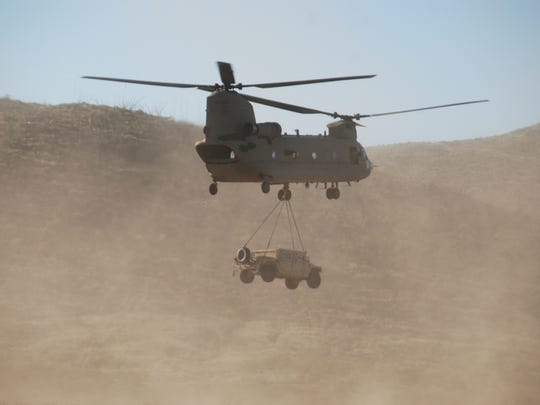 "A Chinook ""sling loads"" a vehicle and transports it during an air assault in the Army Warfighting Assessment."