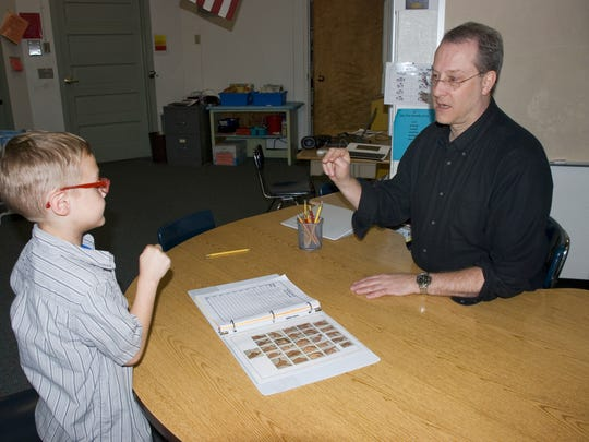 Tim McFarland, a special education teacher at Englewood Elementary, works with a student.