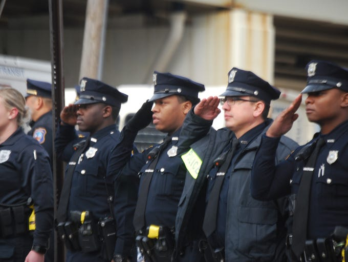 Officers salute as the body of Sgt. Steven Floyd is