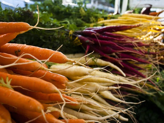 Multicolored carrots on display from local farmers.