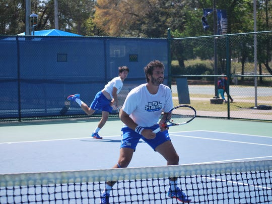 UWF senior Alex Peyrot serves while doubles teammates Pedro Dumont readies himself at the net. Peyrot and Dumont are the No. 1 doubles duo in the Division in 2017.