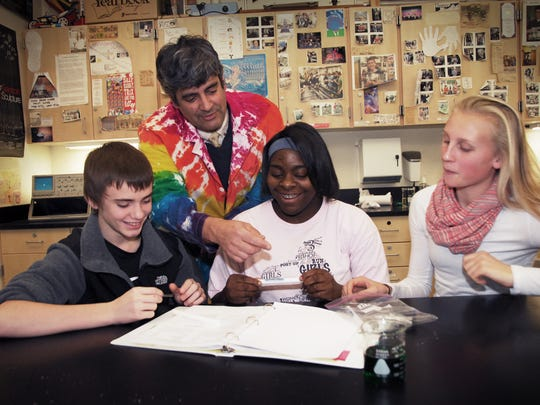 Deven Nipp (left to right), 14, West Salem science teacher Michael Lampert, Angela Mumford, 14 and Brooke Chuhlantseff, 14, examine the science experiment that they created that won a contest to be launched into space en route to the International Space Station in 2012.