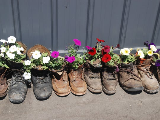 Old boots and shoes around the outside of the Ebert's new round barn are filled with flowers.