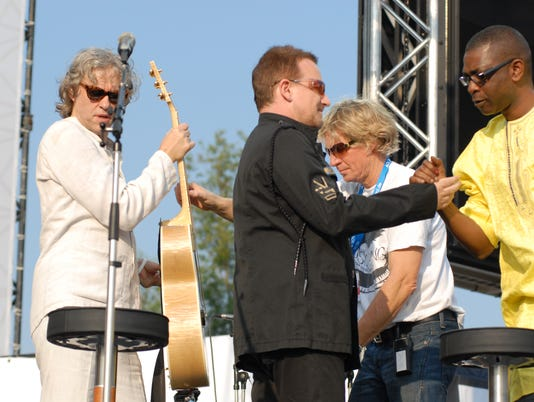 636330267440568411-Dallas-Schoo-hands-a-guitar-to-Bob-Geldof-while-Bono-hobknobs-with-Yousou-N-dore.jpg