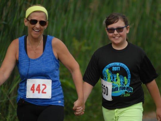 Kim and Alana Dooley finish the mile race at the K's