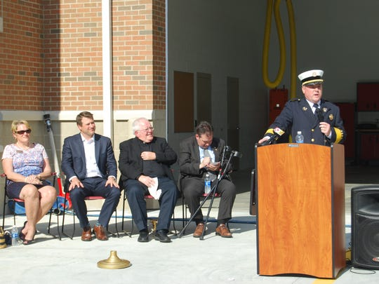 Delhi Township Fire Chief Doug Campbell, right, speaks