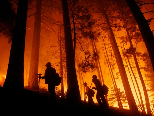 Firefighters watch a prescribed burn at the fire line while fighting the wildfire in South Lake Tahoe, Calif., Sunday, June 24, 2007.