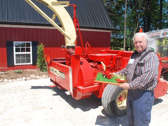 Dale Swoboda, co-chair of the Heritage and Toy Committee for Kewaunee County's Farm Technology Days show, posed with the Gehl chopper that was rendered as a farm toy and with one of the original, locally made choppers that served as a model.