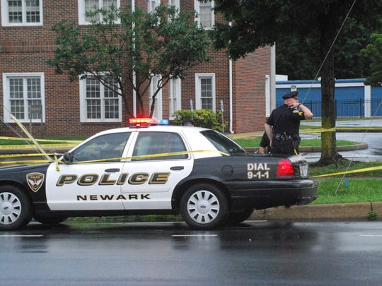 Newark police investigate where a man's body was discovered outside acredit union Friday morning.