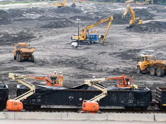 Workers operating heavy equipment at the Kingston Fossil Plant load gondola cars for a train bearing coal ash sludge for disposal in Alabama on Sept. 23, 2009.