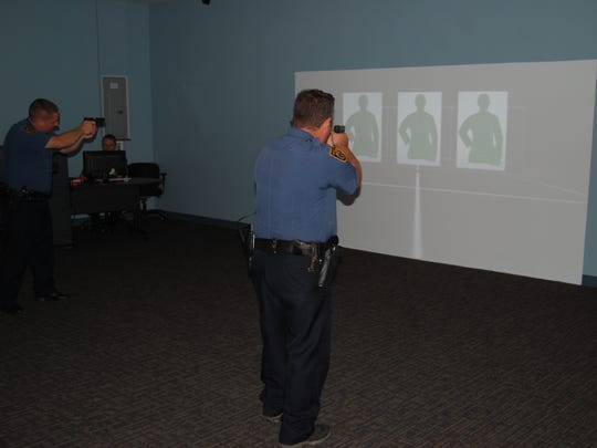 Green Township police officers aim at targets projected by a use of force simulator set up at the department's new training center. The training center opened earlier this year.