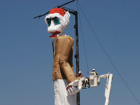 Workers prepare the towering Zozobra marionette for
