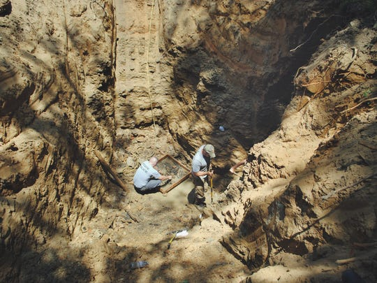 A Kentucky State Police detective searches through the debris from a cistern in 2014,  looking for possible clues in the kidnapping of Heather Teague.