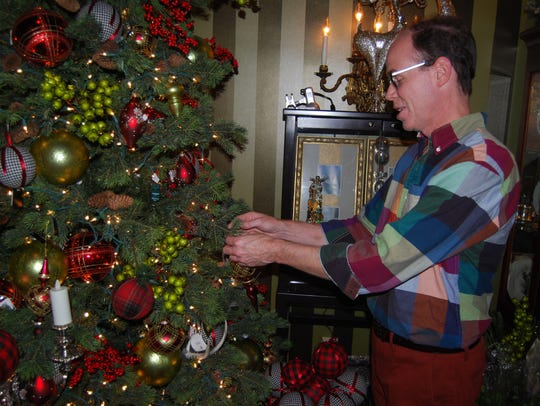 Brad Price, owner of Villa Sanctuary, decorates the store in preparation for the holidays. Price said Small Business Saturday in Milford is a big attraction.