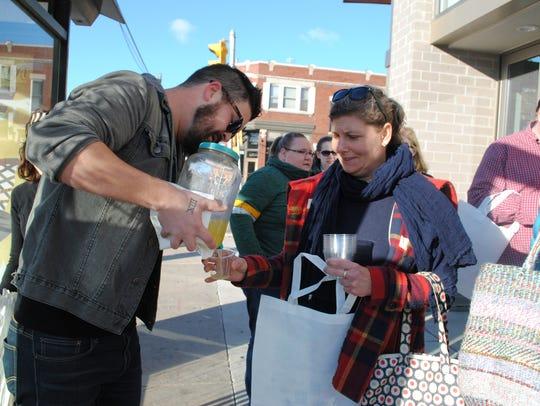 Employee Geoff Hoen pours a mimosa for shopper Stephanie