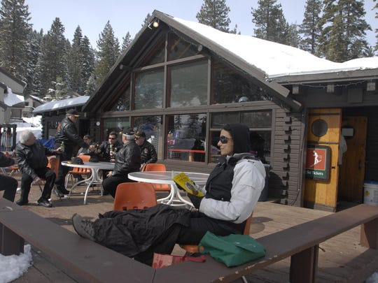 Cinzia Perlingieri reads on the lodge deck at Granlibakken while her family enjoys the hill in 2010.