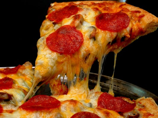 Slice of pepperoni pizza with pulling cheese