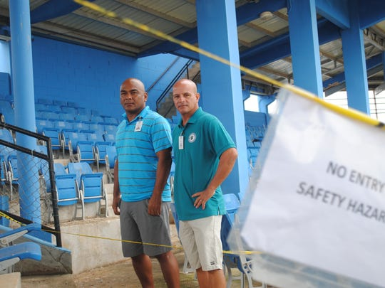 Benjie Pangelinan, left, and Jon Cramer, Parks and Recreation Administrators, stand in an area of Paseo Stadium cordoned off because of falling concrete.