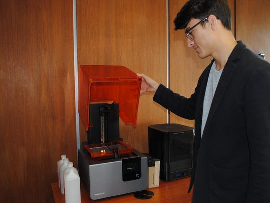 Michael Olaya shows one of Dexter Learning's 3D printers.