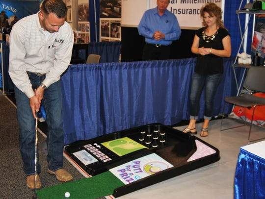 Lee Bearden of Elite San Juan participates in a mini-golf challenge while Trish Cordell watches at a booth for Farmington-based Advertising Ideas during the Four Corners Oil and Gas Conference on Wednesday at McGee Park.