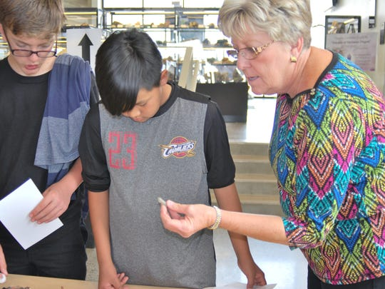 Alicia Blasingame shows Kirtland Middle School eighth-graders Mathew Shelby and Jakari McDonald a rock sample on May 7 at San Juan College.