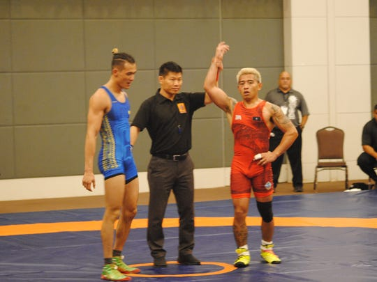 In this file photo, Ethan Aguigui, right, is declared the winner and gold medalist after his victory over Palau's Cristian Nocolescu during the Oceania Wrestling Championships 65kg senior class division.