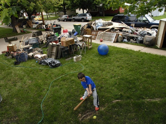 4 year old Brady Schulze plays ball in his grandpaÕs front yard at 382 Wettstein Road in Fond du Lac. Behind him stacked on the terrace and in the front yard is all the household items damaged in Thursdays flooding. Monday, June 16, 2008.