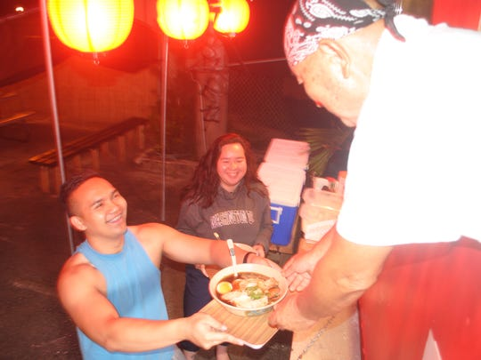 Max Ijima serves ramen to his customers Melchor Castigador, left and Brittany Toves at his food truck in Tamuning on June 12, 2018.