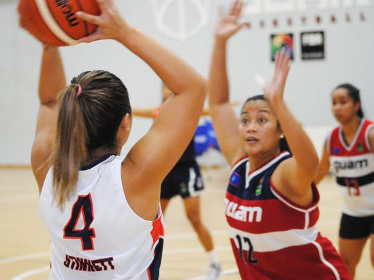 Derin Stinnett, with ball, looks for an open player while defended by Charisse Bolabola during Guam's women's national basketball team practice on June 14, 2018 at the Guam Basketball National Training Center in Tiyan. At rear is Kristene Villena.