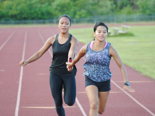 Sprinters Richelle Tugade, left, passes the baton to