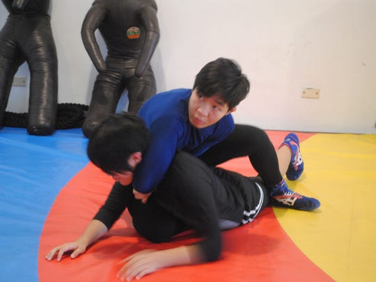 Team Guam wrestler Mia-Lahnee Aquino looks to her coach for guidance as she apoplies a move on her teammate and sister Rckaela Aquino during practice July 10 at Fudoshin gym in Yigo.