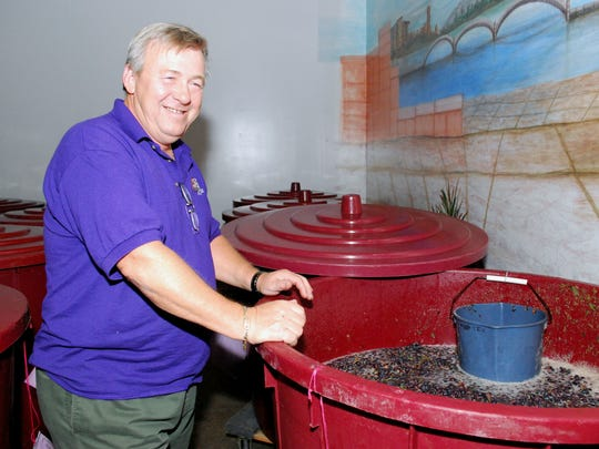 Jim Lowney, who owns Grape Expectations winemaking school in Bridgewater with his wife Mary Ann, checks the yeast culture in a vat of fermenting grapes.