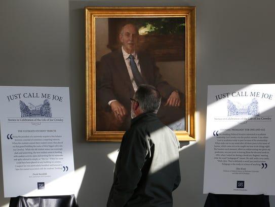 An attendee stands below a portrait of Joe Crowley