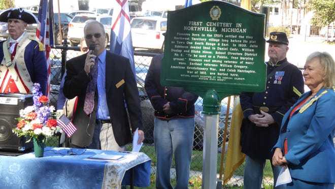 Northville Mayor Ken Roth speaks during the Oct. 8 unveiling of a historic marker at Oakwood Cemetery. He was joined by Kathleen Ripley Leo of the National Society Daughters of the American Colonies, and by reenactors dressed in historic military uniforms.